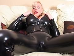 A blond in a tight leather outfit unties herself and uses her toy