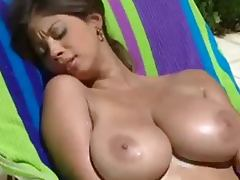 Busty Ashley rubs lotion on herself while lounging